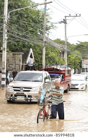 CHIANG MAI THAILAND - SEPTEMBER 28 : Flooding the Chiangmai city.An unidentified elderly man holding a bicycle through the flood on September 28,2011 in Chiangmai Thailand - stock photo