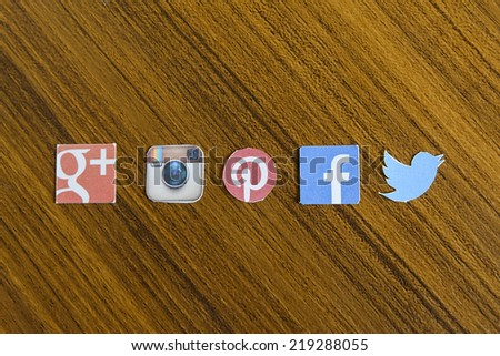 CHIANG MAI, THAILAND - SEPTEMBER 24, 2014: Social media brands printed on sticker and placed on wood table. Include Facebook, Pinterest, Twitter and Google Plus logo. - stock photo