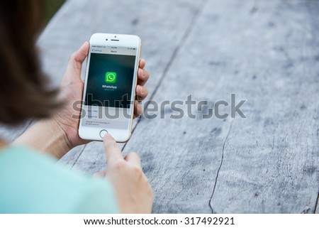 CHIANG RAI, THAILAND - SEPTEMBER 13, 2015: Woman try to use social Internet service WhatsApp screen on blue background. iPhone 6 was created and developed by the Apple inc.