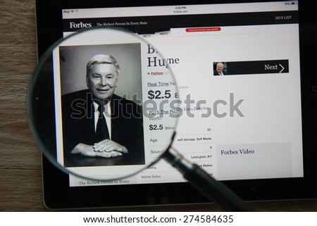 CHIANGMAI, THAILAND - April 30, 2015: Photo of Forbes article page about B. Wayne Hughes on a ipad monitor screen through a magnifying glass.