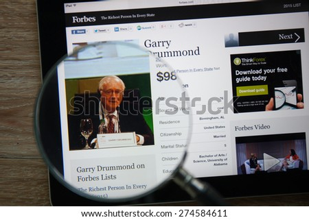 CHIANGMAI, THAILAND - April 30, 2015: Photo of Forbes article page about Garry Drummond on a ipad monitor screen through a magnifying glass.