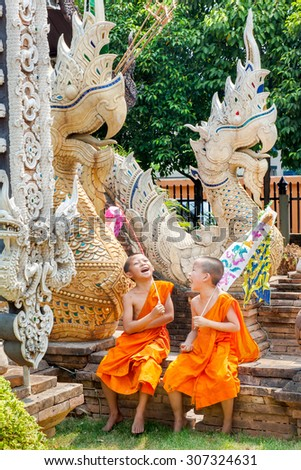 CHIANGMAI, THAILAND-APRIL 14, 2010 : Songkran Festival is celebrated in a traditional New Year's Day, A little monk laughing and decorat tung in the temple Wat LokMoLee. Chiang Mai,Thailand. - stock photo