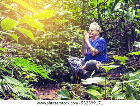 CHIANGMAI, THAILAND, Dec 8, 2016.  a man is sitting and praying on the rock in the jungle  ,vintage tone and light effected