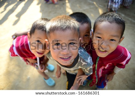CHIANGMAI, THAILAND - December 15, 2012: A group of unidentified street children dressed in tribe costumes welcoming tourists as they pass through their village. - stock photo
