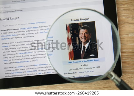 CHIANGMAI, THAILAND - February 26, 2015: Photo of Wikipedia article page about Ronald Reagan on a ipad monitor screen through a magnifying glass. - stock photo