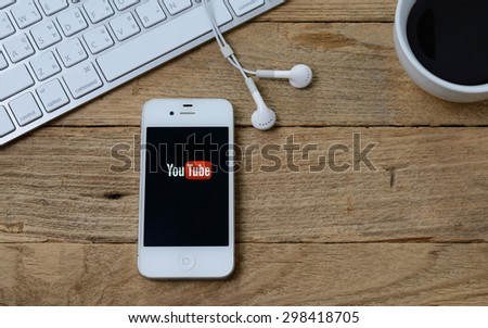 CHIANGMAI,THAILAND - JULY  21, 2015: Brand Apple iPhone 4s with YouTube app on the screen lying on desk with headphones. YouTube is the popular online video-sharing website, - stock photo