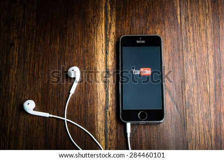 CHIANGMAI, THAILAND -JUNE 05, 2015:Brand new Apple iPhone with YouTube app on the screen lying on desk with headphones. - stock photo