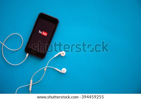 CHIANGMAI,THAILAND - MARCH 22, 2016:Brand new Apple iPhone 6 with YouTube app on the screen lying on desk with headphones. YouTube is the popular online video-sharing website, - stock photo