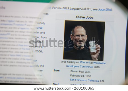 CHIANGMAI, THAILAND - March 5, 2015: Photo of Wikipedia article page about Steve Jobs on a ipad monitor screen through a magnifying glass. - stock photo