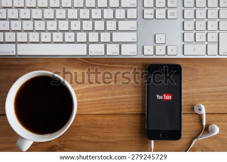 CHIANGMAI, THAILAND -MAY 19, 2015:Brand new Apple iPhone  with YouTube app on the screen lying on desk with headphones. YouTube is the popular online video-sharing website, - stock photo