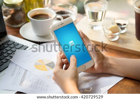 CHIANGMAI,THAILAND - MAY 10 ,2016 :Woman holding iPhone 6 plus with social network service LinkedIn on the screen. iPhone 6 plus was created and developed by the Apple inc. - stock photo