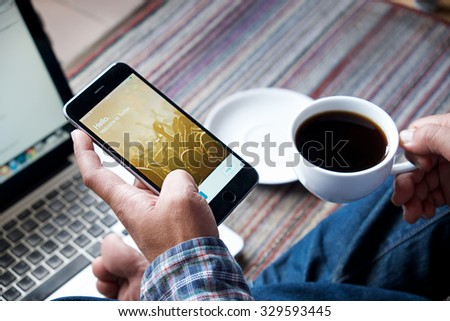CHIANGMAI, THAILAND -OCT 20, 2015A man hold:new Apple iPhone 6 Plus open Twitter application,Twitter is an online social networking and microblogging service that enables users to send and read tweets - stock photo