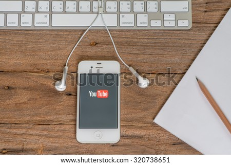 CHIANGMAI,THAILAND - September 26, 2015: Brand Apple iPhone 4s with YouTube app on the screen lying on desk with headphones. YouTube is the popular online video-sharing website, - stock photo