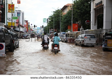 CHIANGMAI , THAILAND - SEPTEMBER 28: Thai monsoon People on motorcycle drive through flooded streets on September 28, 2011 in Chang Karn , Muang , Chiangmai , Thailand. - stock photo