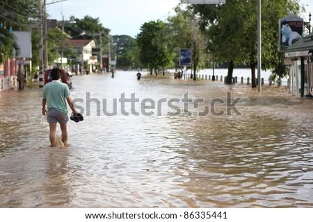 CHIANGMAI , THAILAND - SEPTEMBER 30 : Thai monsoon People walking through flooded streets on September 28, 2011 in Wat Gate , Muang , Chiangmai , Thailand. - stock photo