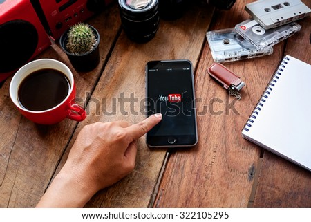 CHIANGMAI, THAILAND -SPE 30, 2015:Brand new Apple iPhone with YouTube app on the screen lying on desk with headphones. - stock photo