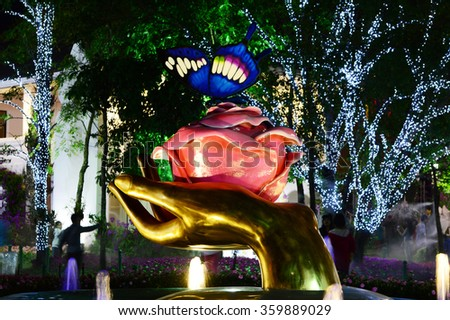 CHIANGRAI - DECEMBER 28:Silhouette and Golden hand hold flower with butterfly in Chiangrai ASEAN Flowers Festival 2015 is one of the biggest flower festival  in Chiangrai , Thailand - stock photo