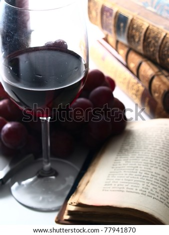 chianti reserve wine, glass, grapes and old books - stock photo