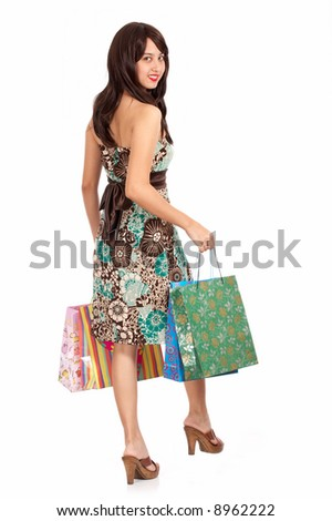 chic and stylish woman walking ahead - holding some shopping bags - stock photo
