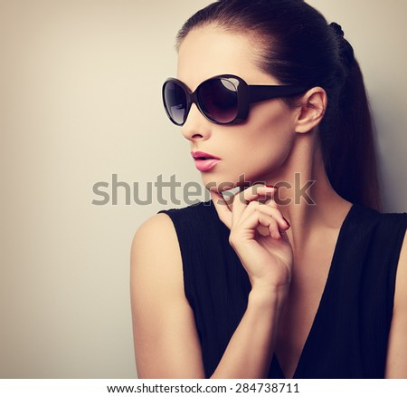 Chic beautiful young female model profile in fashion sunglasses posing. Vintage color closeup portrait