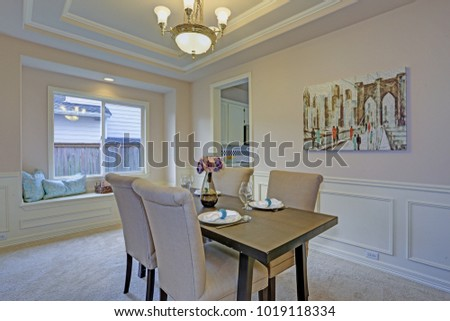 Chic Dining Room With Light Grey Walls Accented Wall Panel Mouldings Under Tray Ceiling
