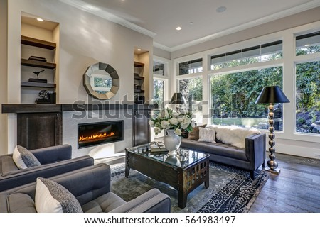 Chic Living Room Filled With Built In Cabinets Flanking Round Mirror Atop Grey Tile Fireplace