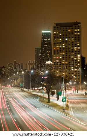 Chicago at night centered on the John Hancock Center with a busy Lake Shore Drive in the foreground. - stock photo