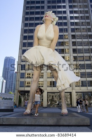 CHICAGO - AUGUST 25: An unidentified tourist poses in front of a 26 foot tall sculpture of Marilyn Monroe in Chicago on August 25, 2011. Created by artist Seward Johnson, the work is on Michigan Avenue. - stock photo