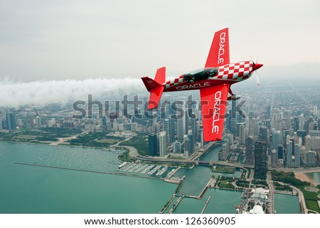 CHICAGO - AUGUST 16: Sean Tucker of Team Oracle flies in front of the Chicago skyline during the Chicago Air and Water Show Media Day on August 16, 2012 in Chicago. - stock photo