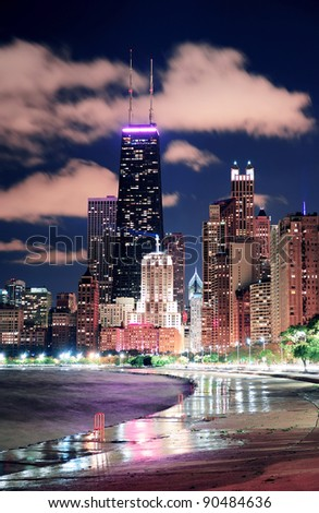 Chicago city urban skyscraper at night at downtown lakefront illuminated with Lake Michigan and water reflection viewed from North Avenue Beach. - stock photo