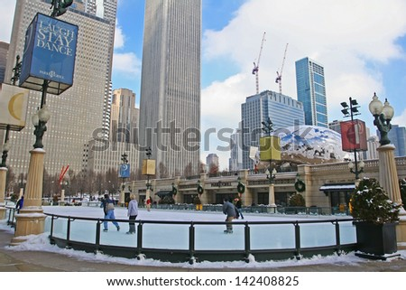 CHICAGO,IL-FEB 09:Unidentified people enjoy ice skating near Skygate Bean against high building towers and blue sky at Millennium Park on February 09, 2008 in Chicago, IL USA. - stock photo