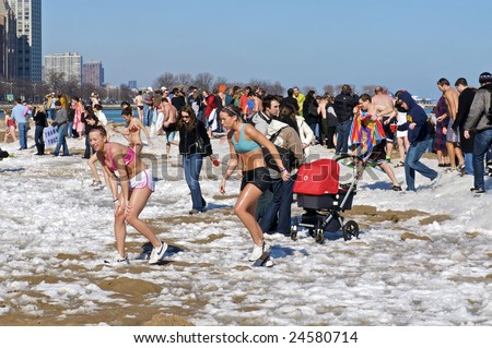 CHICAGO, IL - FEBRUARY 7: Swimmers exit the water at the Lakeview Polar Bear Club's 8th Annual polar plunge on February 7, 2009 at Oak Street Beach in Chicago, IL - stock photo