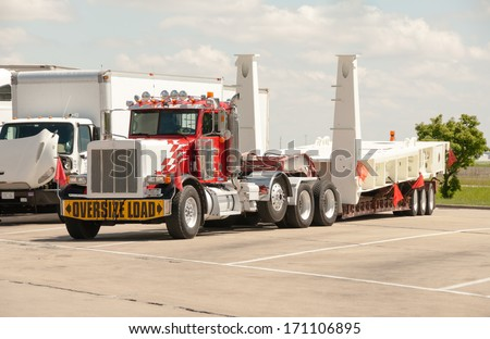 Chicago, IL June 03: Oversize load of heavy machinary on a semi flatbad truck at a rest stop on June 03, 2013. - stock photo