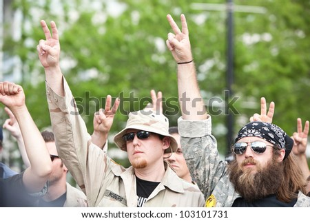 CHICAGO, IL- MAY 20: Iraq War Veterans show peace signs protesting the 25th NATO Summit. The first summit held outside of Washington, D.C. in the United States, Chicago, Illinois, May 20-21, 2012. - stock photo