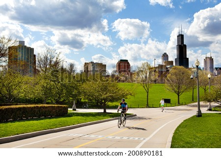 CHICAGO, IL - May 4, 2014: People enjoy the lakefront pathway at Northerly island near downtown on one of the first warm days of spring, May 4, 2014, Chicago, Illinois.  - stock photo