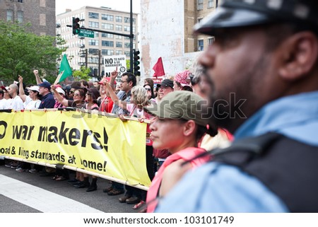 CHICAGO, IL- MAY 20: Police stand guard while protesters march at the 25th NATO Summit. The first summit to be held outside of Washington, D.C. in the United States, Chicago, IL, May 20-21, 2012. - stock photo