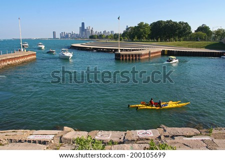 CHICAGO, IL, US - JULY 30, 2007: Unidentified people on Canoes and Yachts sailing at Uptown beach, the shores of lake Michigan, in Summer time. - stock photo