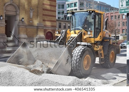 CHICAGO, ILLINOIS - APRIL 15, 2016: Construction front loader operator grades gravel for West Illinois Street sewer replacement project. - stock photo