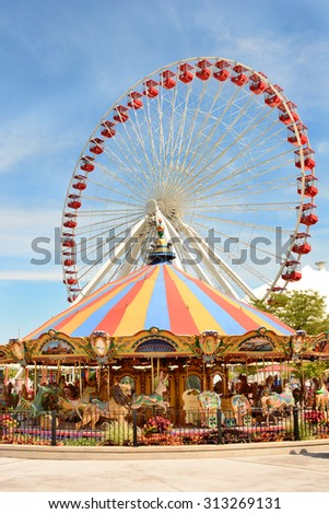 CHICAGO, ILLINOIS - AUGUST 22, 2015: Navy Pier rides. The Ferris Wheel and Carousel are popular attractions on Chicago's Navy Pier on Lake Michigan.  - stock photo