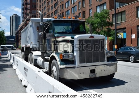 CHICAGO, ILLINOIS - JULY 25: Dump truck stages next to high rise construction barricades on July 25, 2016 in near north side river north.  - stock photo