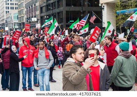 CHICAGO, ILLINOIS - MAY 1, 2016: The Aleppo is Burning Syrian group marches at the May Day rally to raise awareness of the crisis in Syria. - stock photo