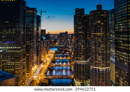 CHICAGO, ILLINOIS - NOVEMBER 23, 2013: View of Chicago River at dusk with the mixed-use residential/commercial building complex of Marina City in the foreground. - stock photo