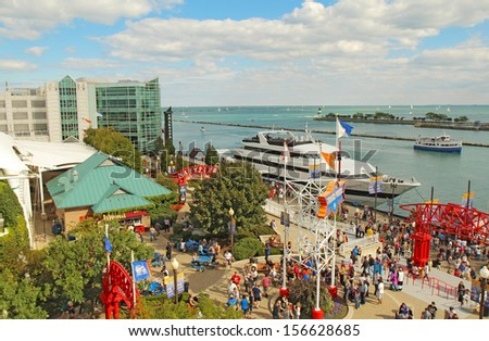 CHICAGO, ILLINOIS - SEPTEMBER 4: Tourists and boats on the lakefront at Navy Pier in Chicago, Illinois on September 4, 2011. The Pier is a popular destination with many attractions on Lake Michigan. - stock photo