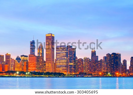 Chicago Illinois skyline at sunset with illuminated downtown buildings - stock photo