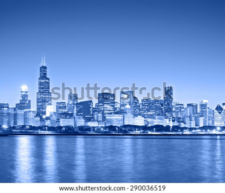 Chicago Illinois USA, blue color processed panorama of city downtown skyline at sunset with illuminated buildings, park and lake - stock photo
