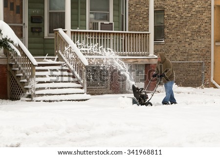 CHICAGO, ILLINOIS,, USA- Nov 21: A man is cleaning snow off sidewalk with a snow blower on Nov 21, 2015 in Chicago, Illinois, USA - stock photo