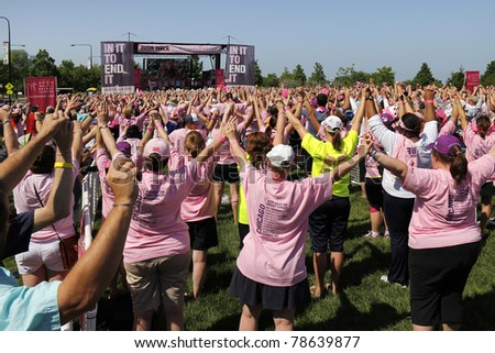 CHICAGO - JUNE 5: Participants raising their hands at the final ceremony festivities at the Avon Walk for Breast Cancer outside Soldier Field on June 5, 2011 in Chicago, IL. - stock photo
