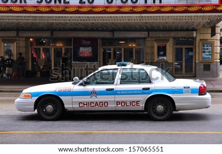 CHICAGO - JUNE 26: People walk past police car on June 26, 2013 in Chicago. Chicago Police Department is one of oldest police forces in the world, dating back to 1837. - stock photo