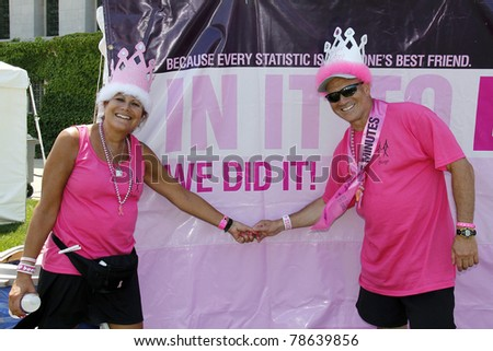 "CHICAGO - JUNE 5: Two participants in front of a ""We Did It!"" poster at the Avon Walk for Breast Cancer outside Soldier Field on June 5, 2011 in Chicago, IL. - stock photo"