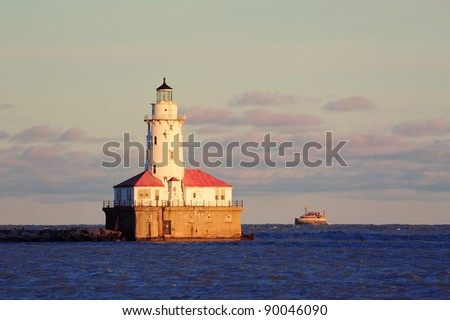 Chicago Light House with boat in Lake Michigan with cloud and blue sky at sunset.